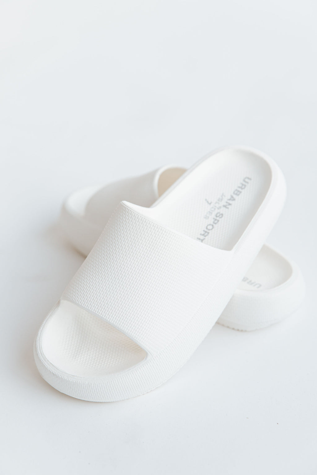 The Squeezy Sandal in White, studio shoot; front view