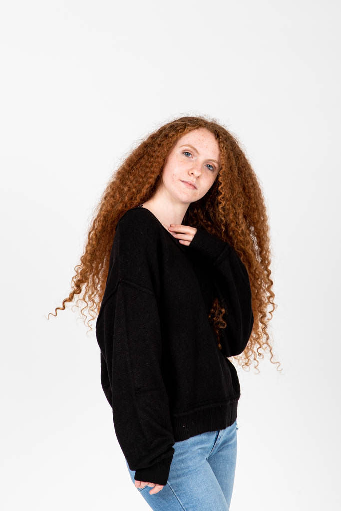 The Wynn Cozy V-Neck Pullover in Black, studio shoot; side view