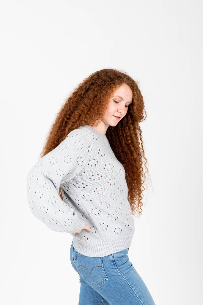 The Rickman Crochet Pattern Sweater in Light Grey, studio shoot; side view