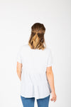 The Hattie Ruffle Peplum Blouse in Light Grey, studio shoot; back view