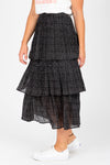 The Molly Tiny Dot Tiered Skirt in Black, studio shoot; side view