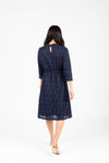 The Othello Lace Ruffle Dress in Navy, studio shoot; back view