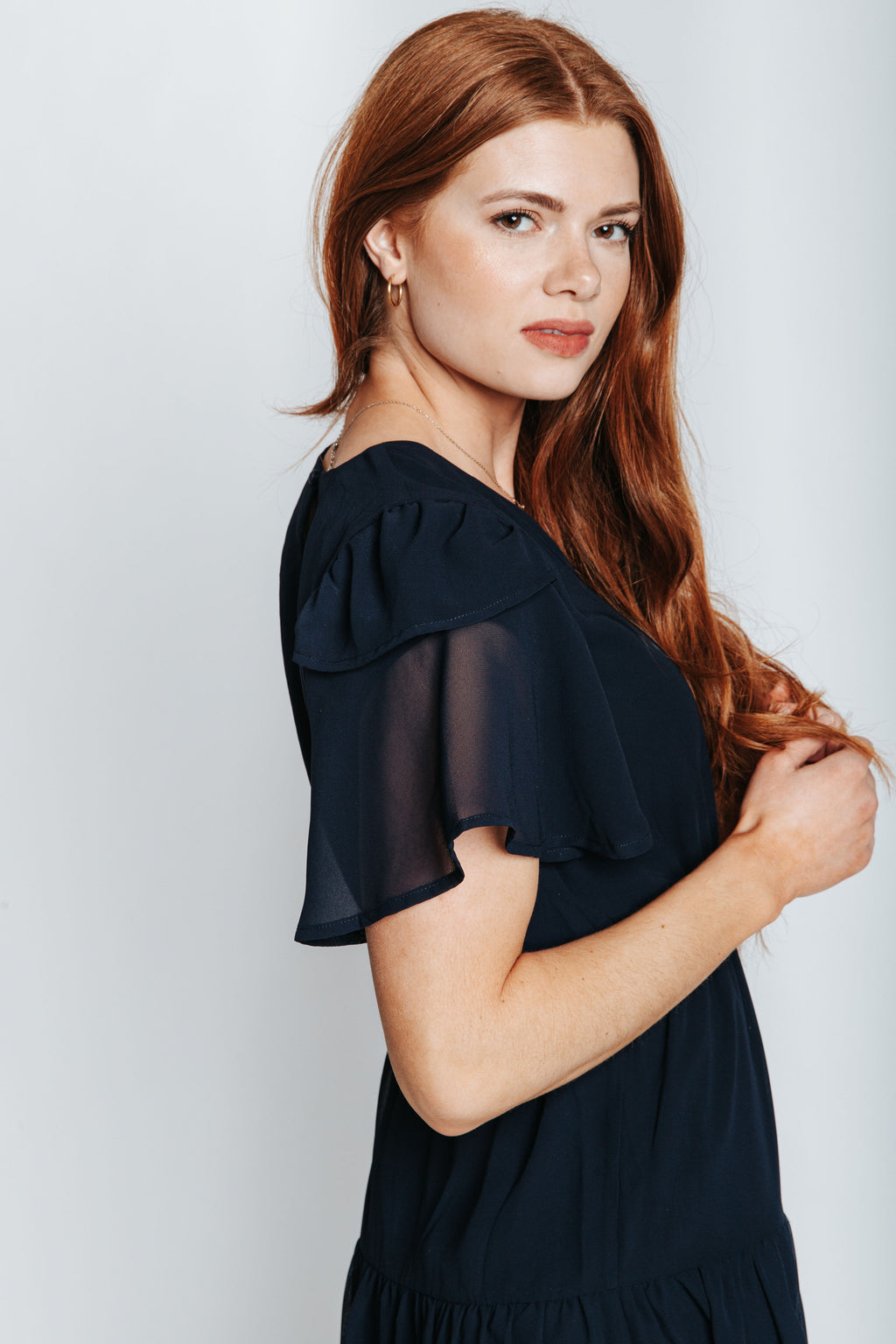 The Amara Ruffle Detail Dress in Navy, studio shoot; side view
