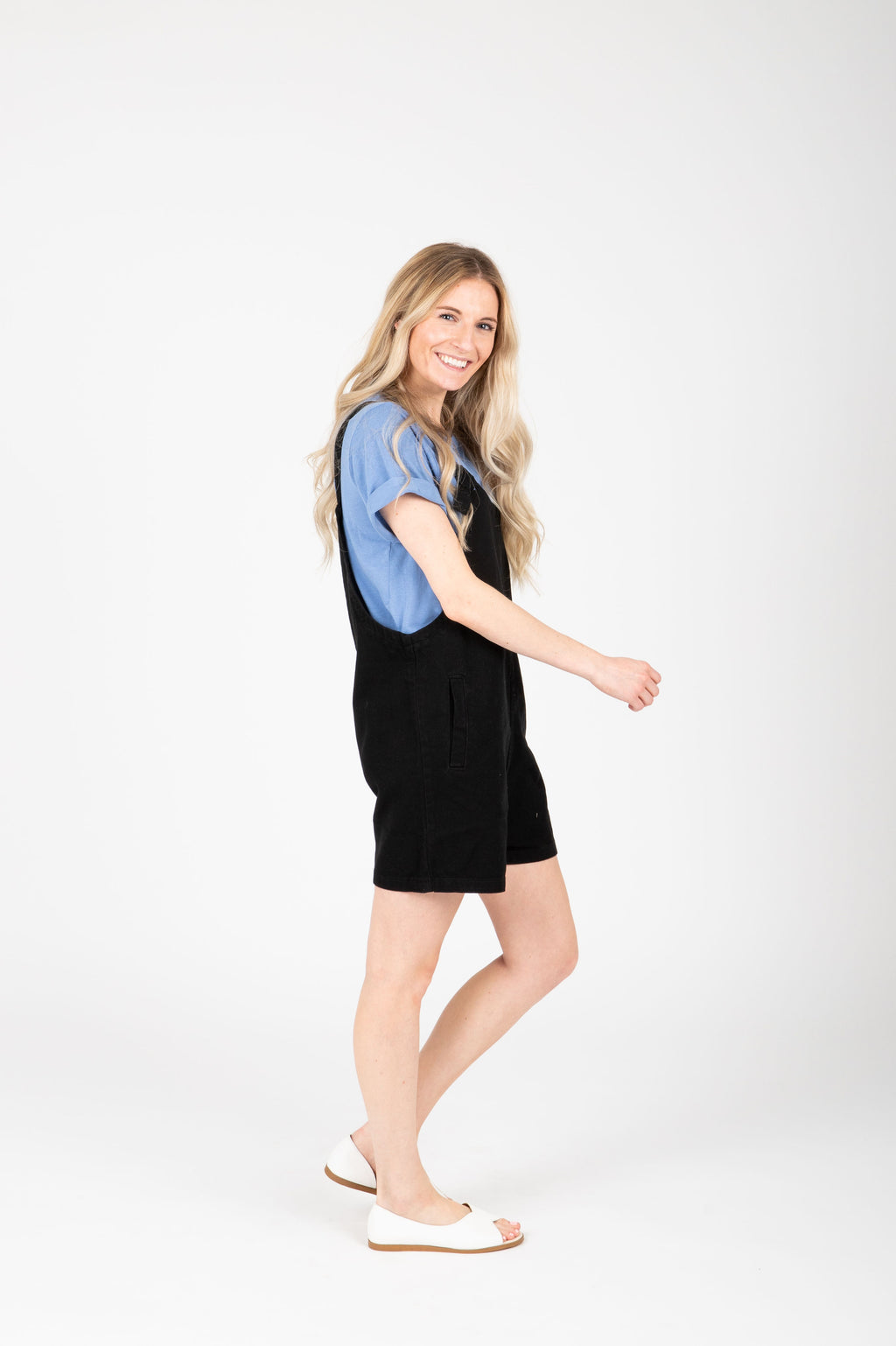 The Mina Shortie Overalls in Black, studio shoot; side view