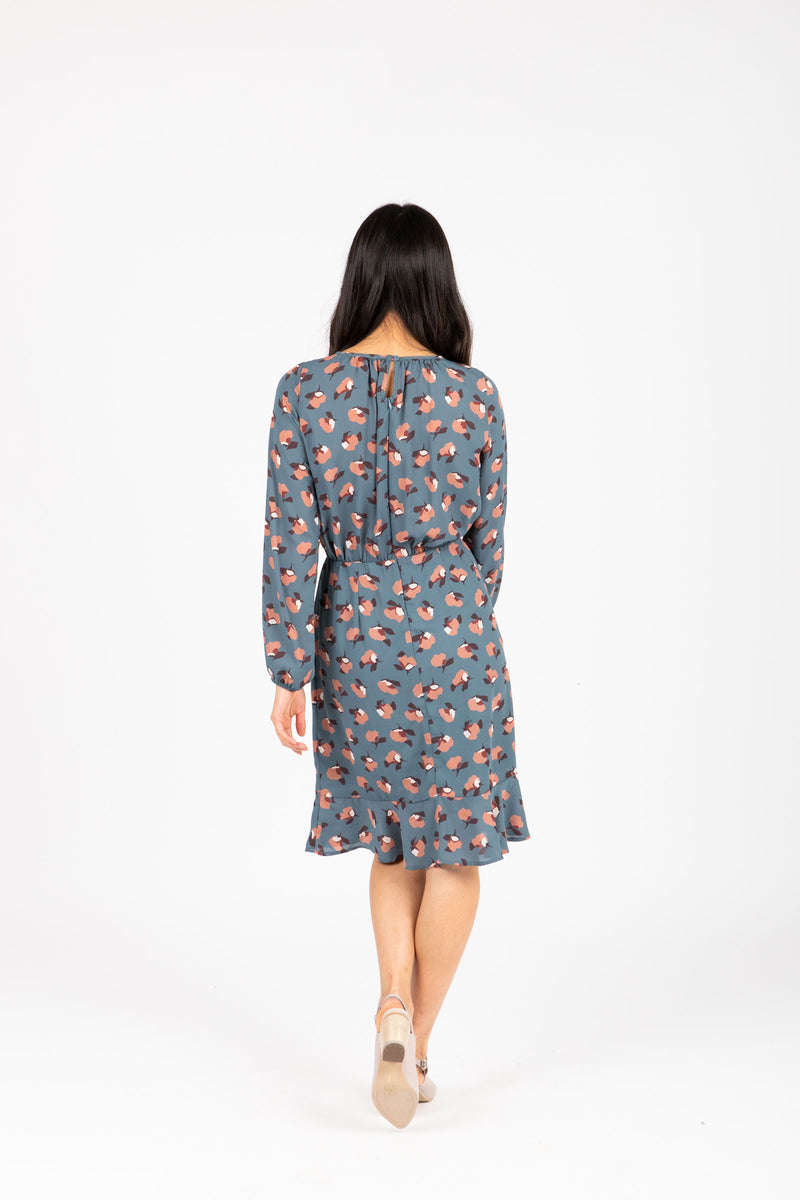 The Dalila Floral Ruffle Dress in Dusty Blue, studio shoot; back view