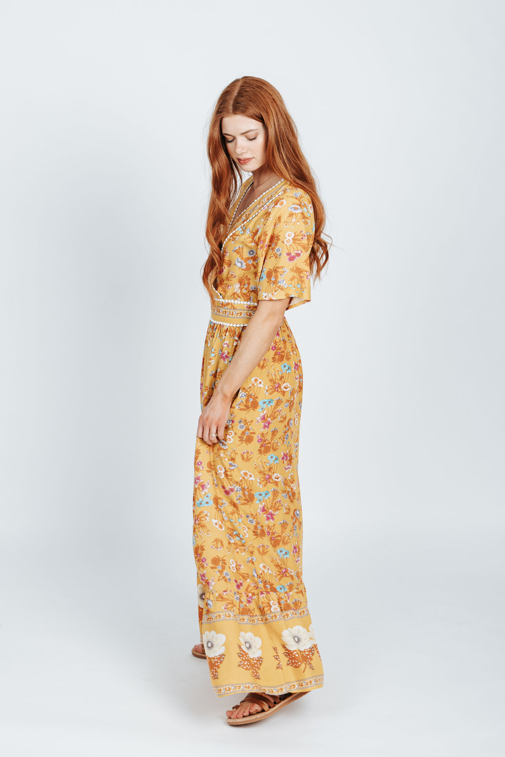 The Rico V-Neck Patterned Maxi Dress in Mustard, studio shoot; side view