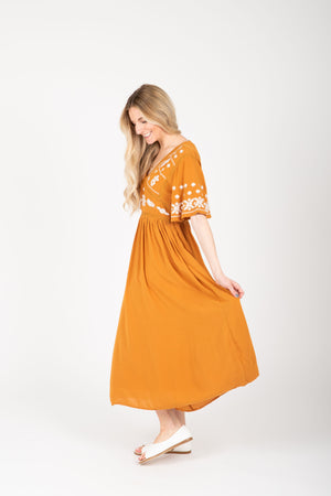 The Cadence Embroidered Detail Dress in Golden, studio shoot; side view