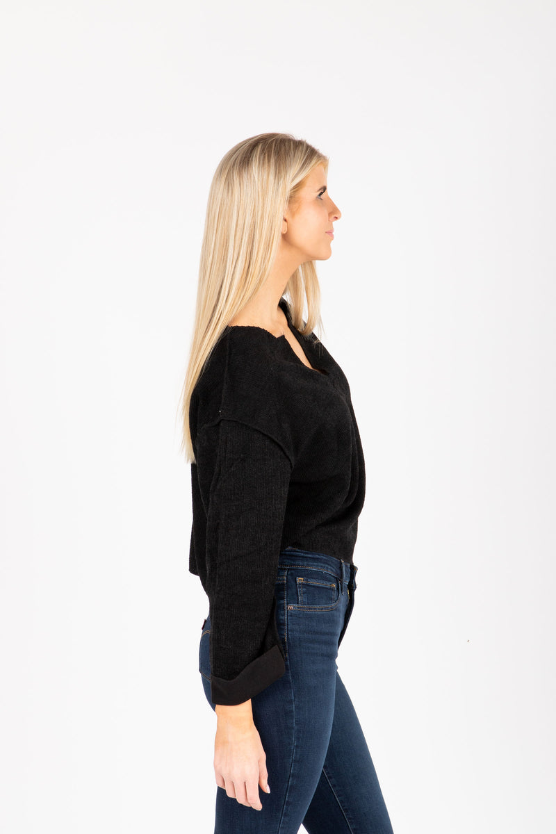 The Chief Slit Sweater in Black, studio shoot; side view