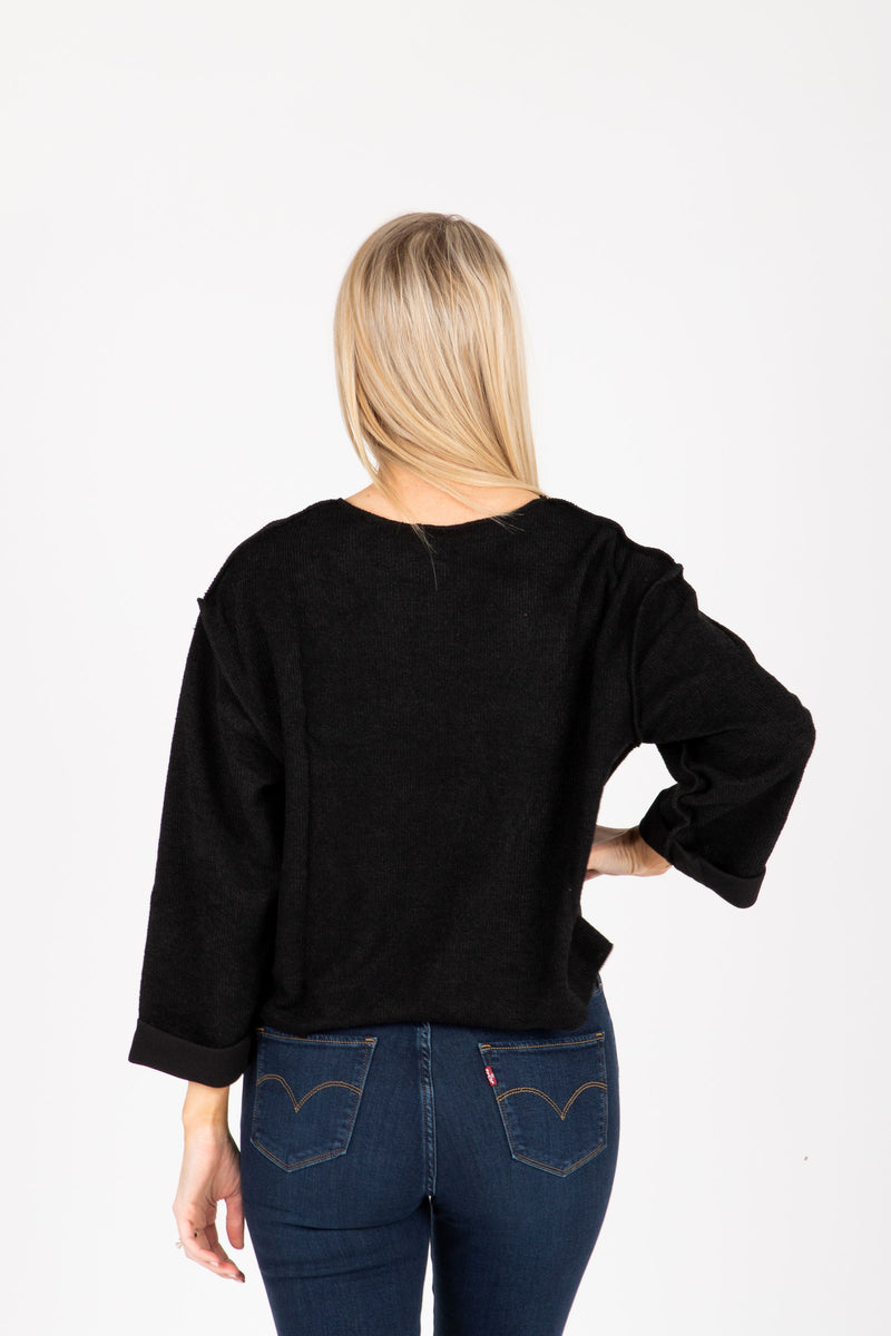 The Chief Slit Sweater in Black, studio shoot; back view