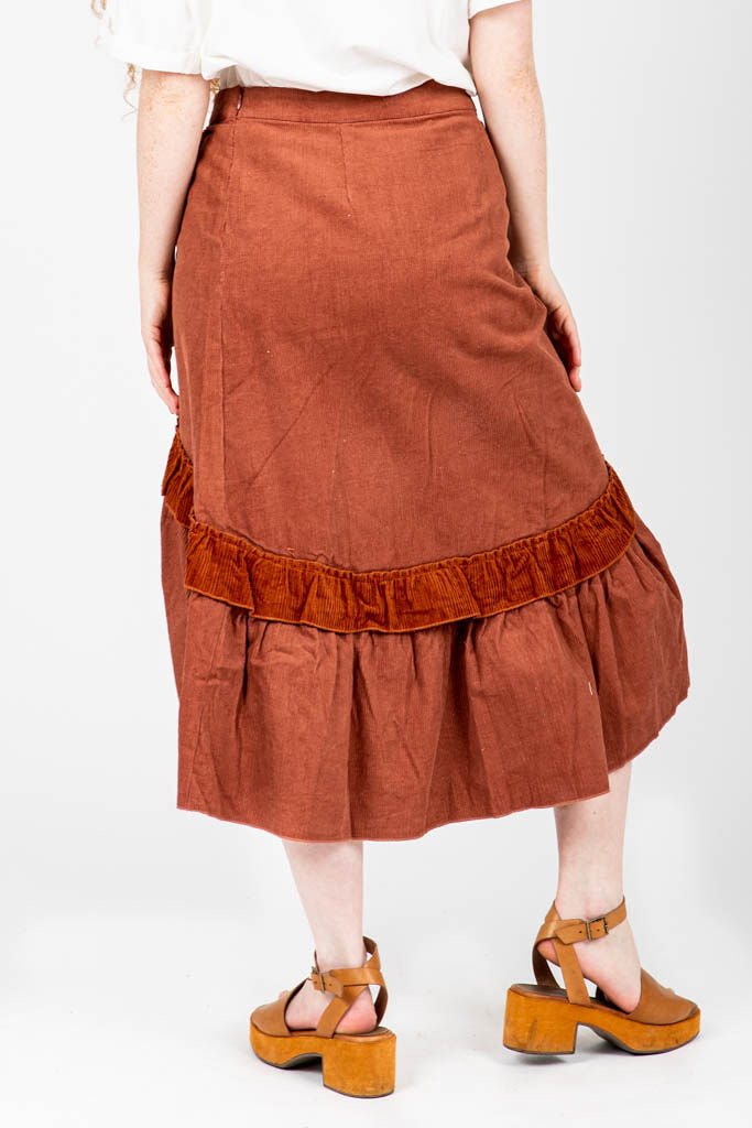 The Coltrane Corduroy Ruffle Skirt in Brick, studio shoot; back view