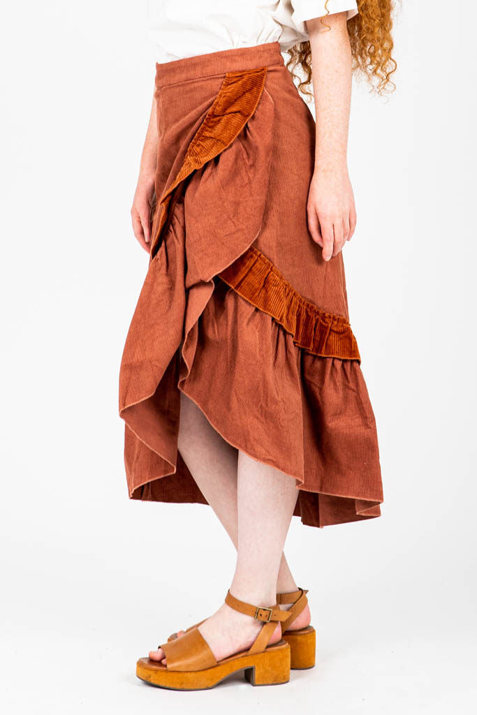 The Coltrane Corduroy Ruffle Skirt in Brick, studio shoot; side view