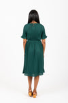 Piper & Scoot: The Versus Pleated Midi Dress in Emerald, studio shoot; back view