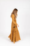 The Luca Floral Maxi Dress in Mustard, studio shoot; side view