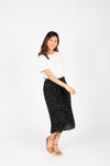 The Gemma Tiny Dot Button Skirt in Black, studio shoot; front view