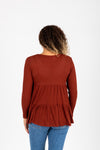 The Mona Waffle Peplum Blouse in Brick, studio shoot; back view