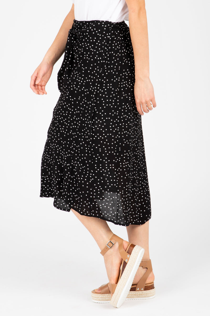 The Gemma Tiny Dot Button Skirt in Black, studio shoot; side view