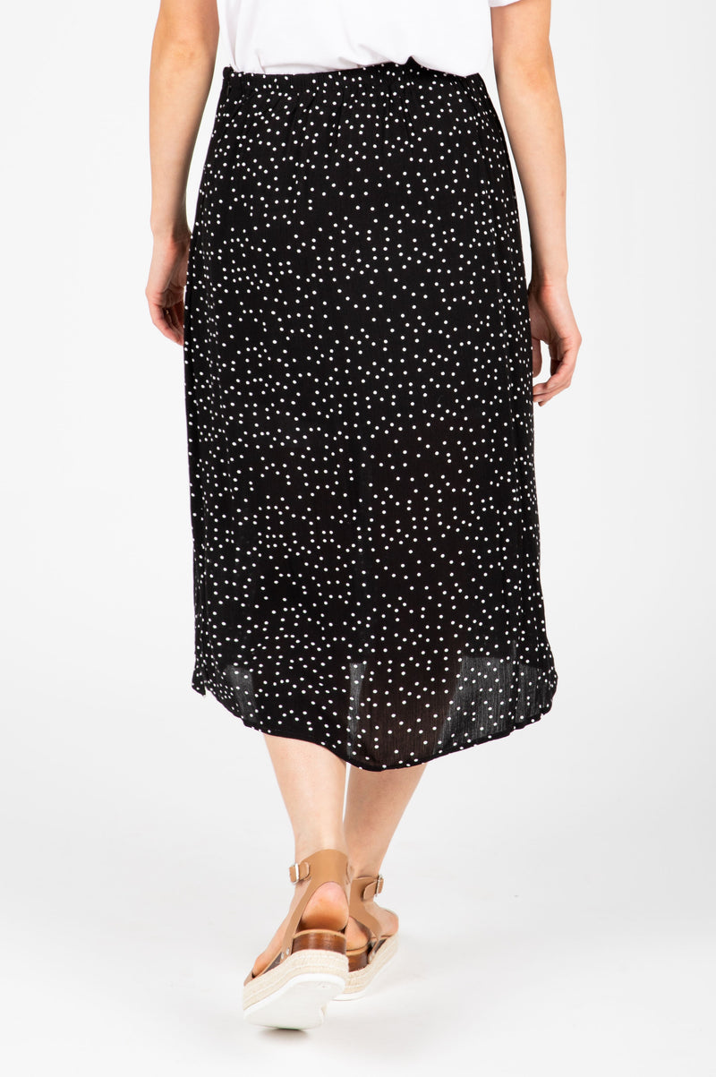 The Gemma Tiny Dot Button Skirt in Black, studio shoot; back view