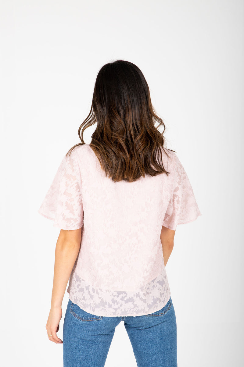 The Morgan Lace Flutter Blouse in Blush, studio shoot; back view