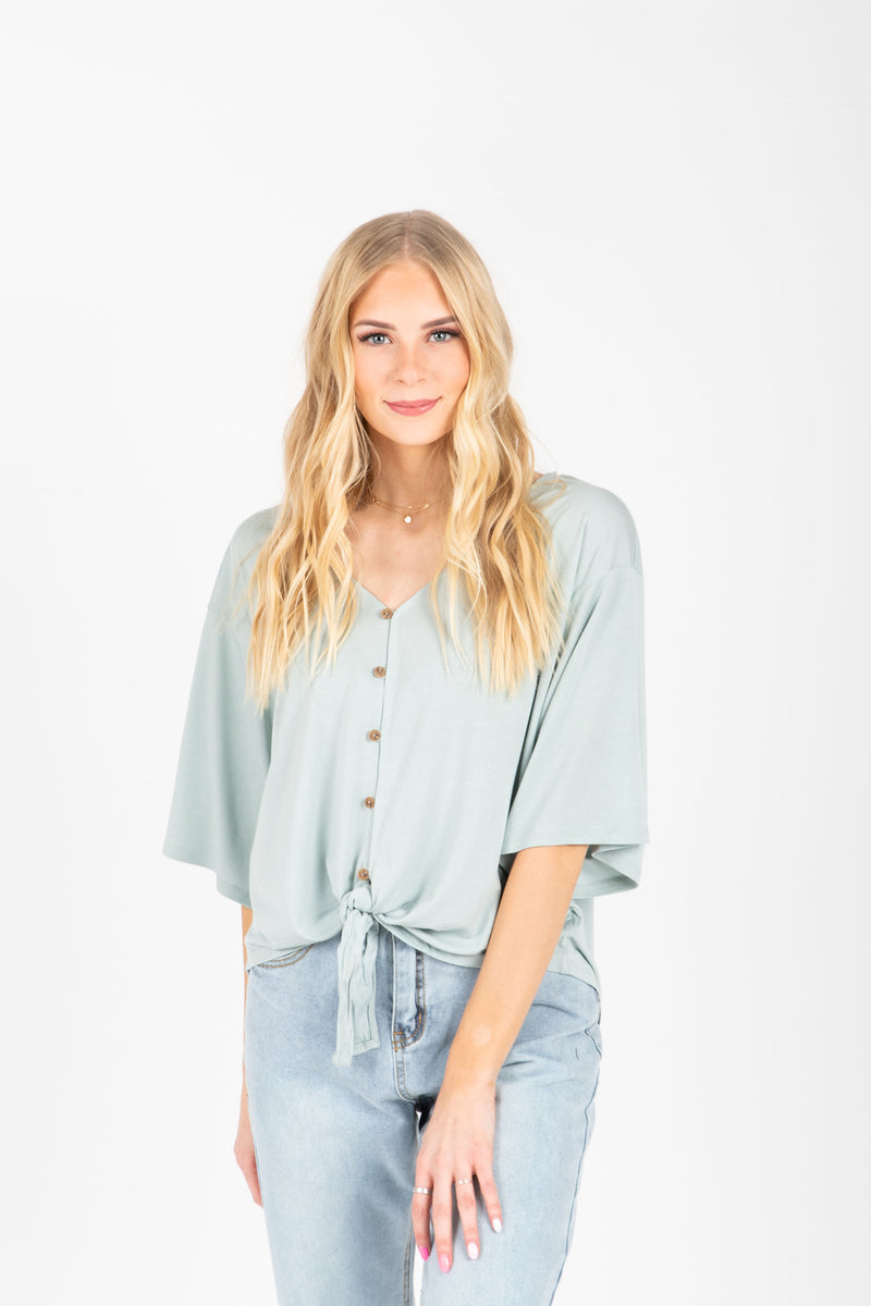 The Espen Button Tie Front Blouse in Sage, studio shoot; front view