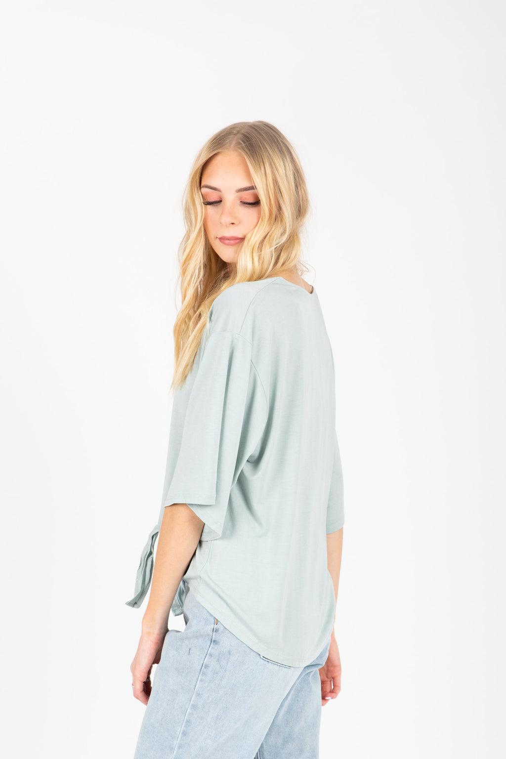 The Espen Button Tie Front Blouse in Sage, studio shoot; side view