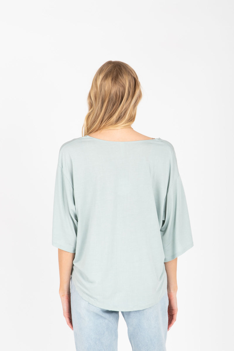 The Espen Button Tie Front Blouse in Sage, studio shoot; back view