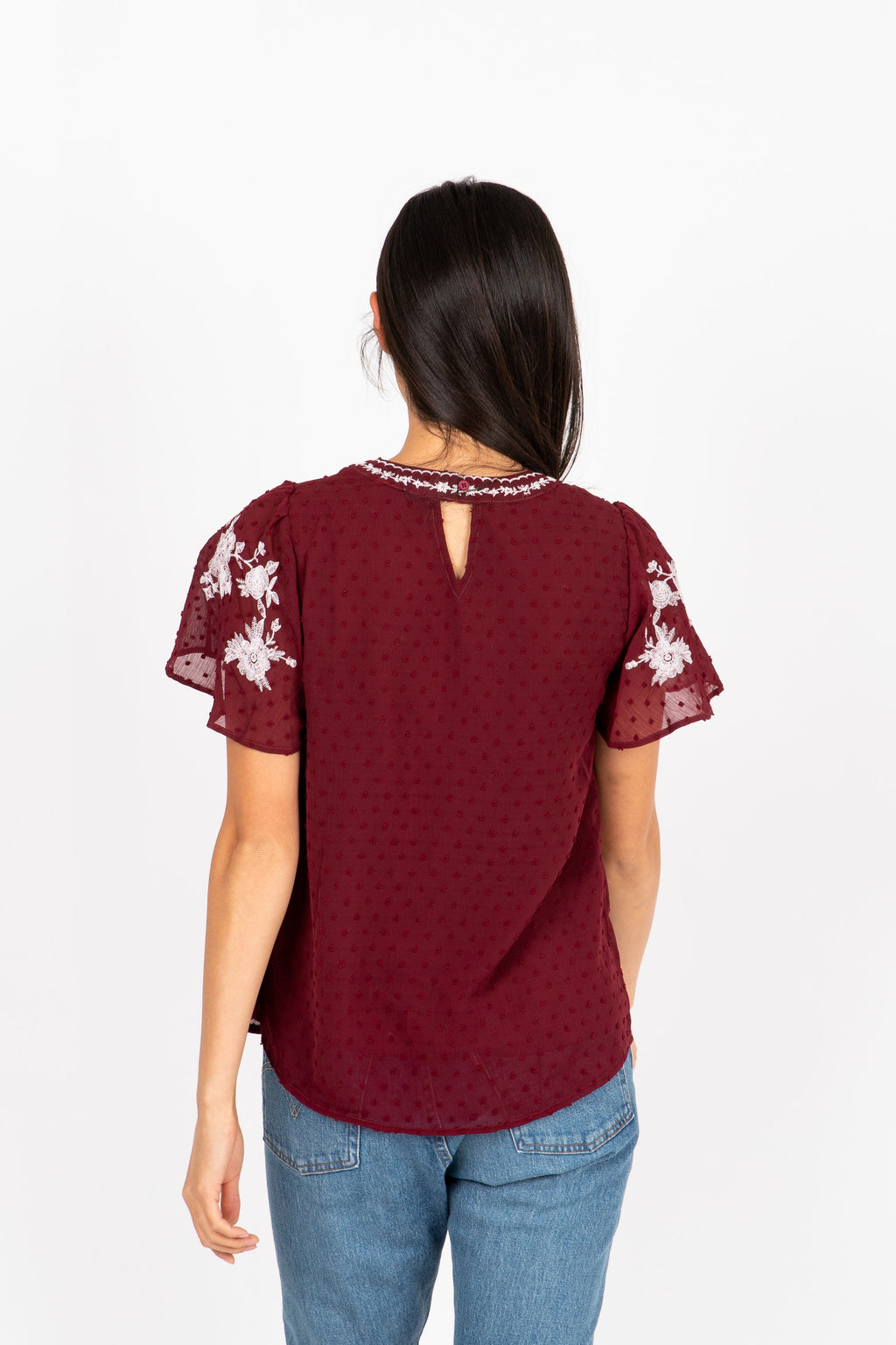 The Fixate Embroidered Swiss Dot Blouse in Burgundy- studio shoot; back view