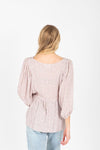 The Larkyn Floral Peplum Blouse in Lavender, studio shoot; back view
