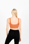 The Moody Ribbed Crop Tank in Persimmon, studio shoot; back view