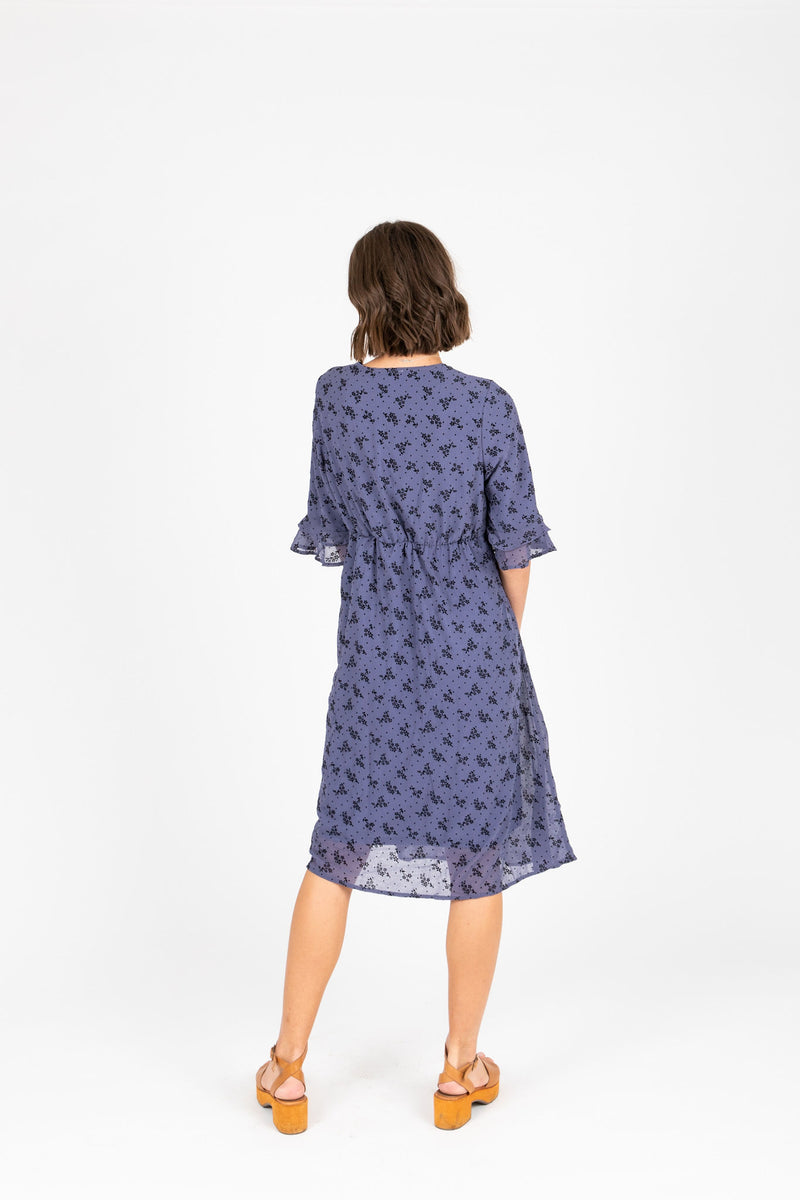 The Gabby Floral Detail Dress in Dusty Blue, studio shoot; back view