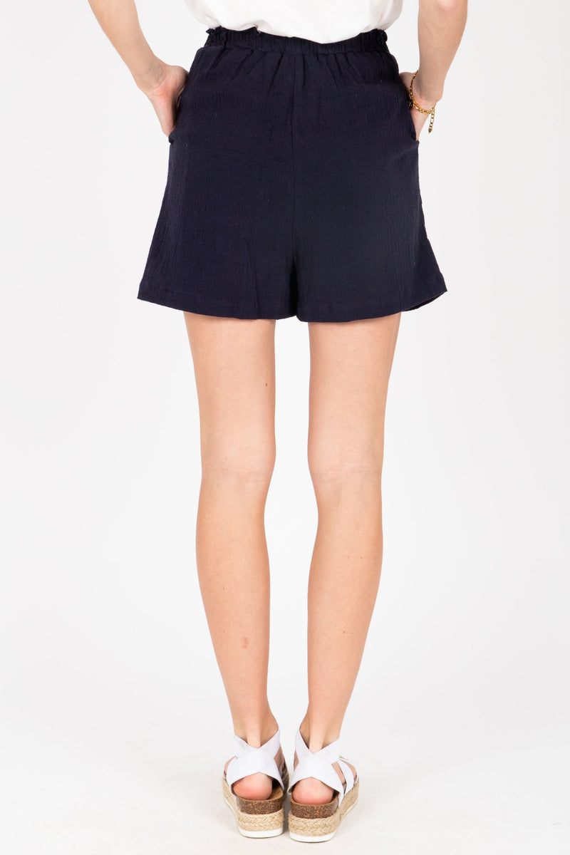 The Rem Embroidered Shorts in Navy, studio shoot; back view