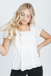 The Christie Smocked Ruffle Blouse in White, studio shoot; front view
