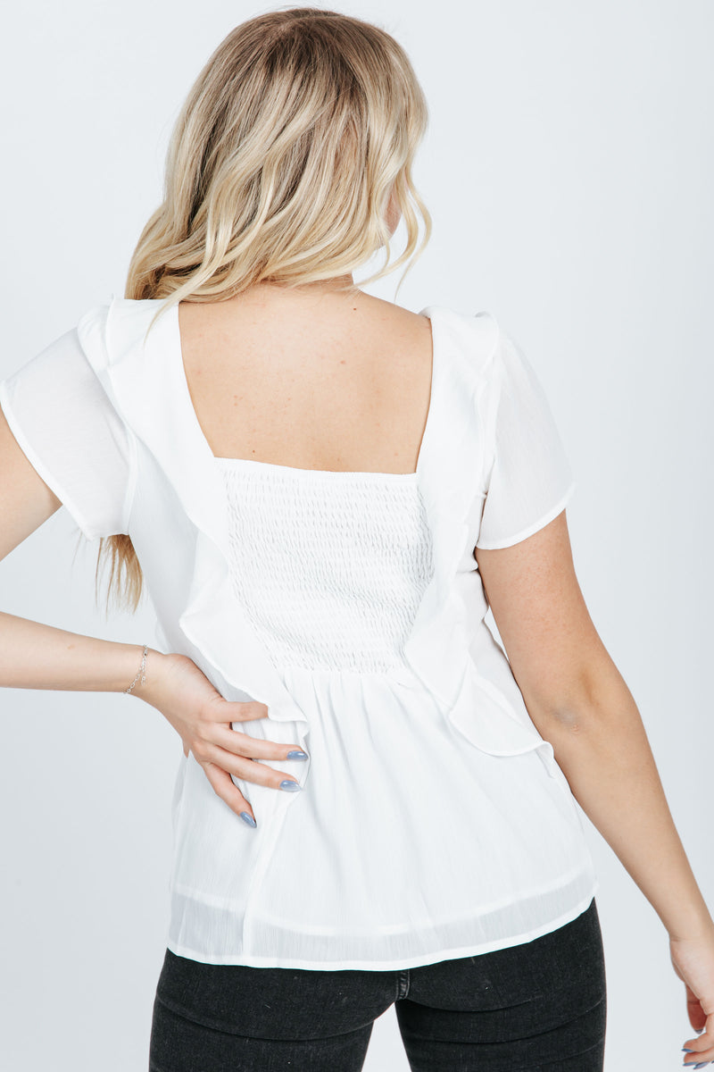 The Christie Smocked Ruffle Blouse in White, studio shoot; back view