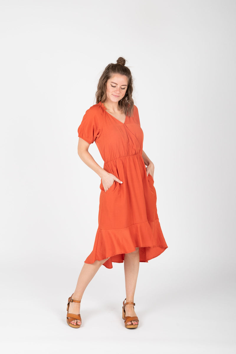 The Ingrid Ruffle Dress in Tangerine, studio shoot; front view