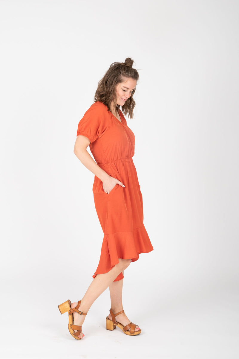 The Ingrid Ruffle Dress in Tangerine, studio shoot; side view
