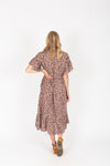 The Brooks Wrap Front Patterned Dress in Mauve, studio shoot; back view