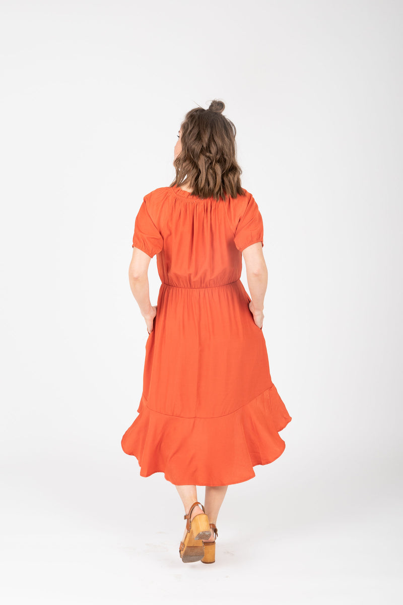 The Ingrid Ruffle Dress in Tangerine, studio shoot; back view