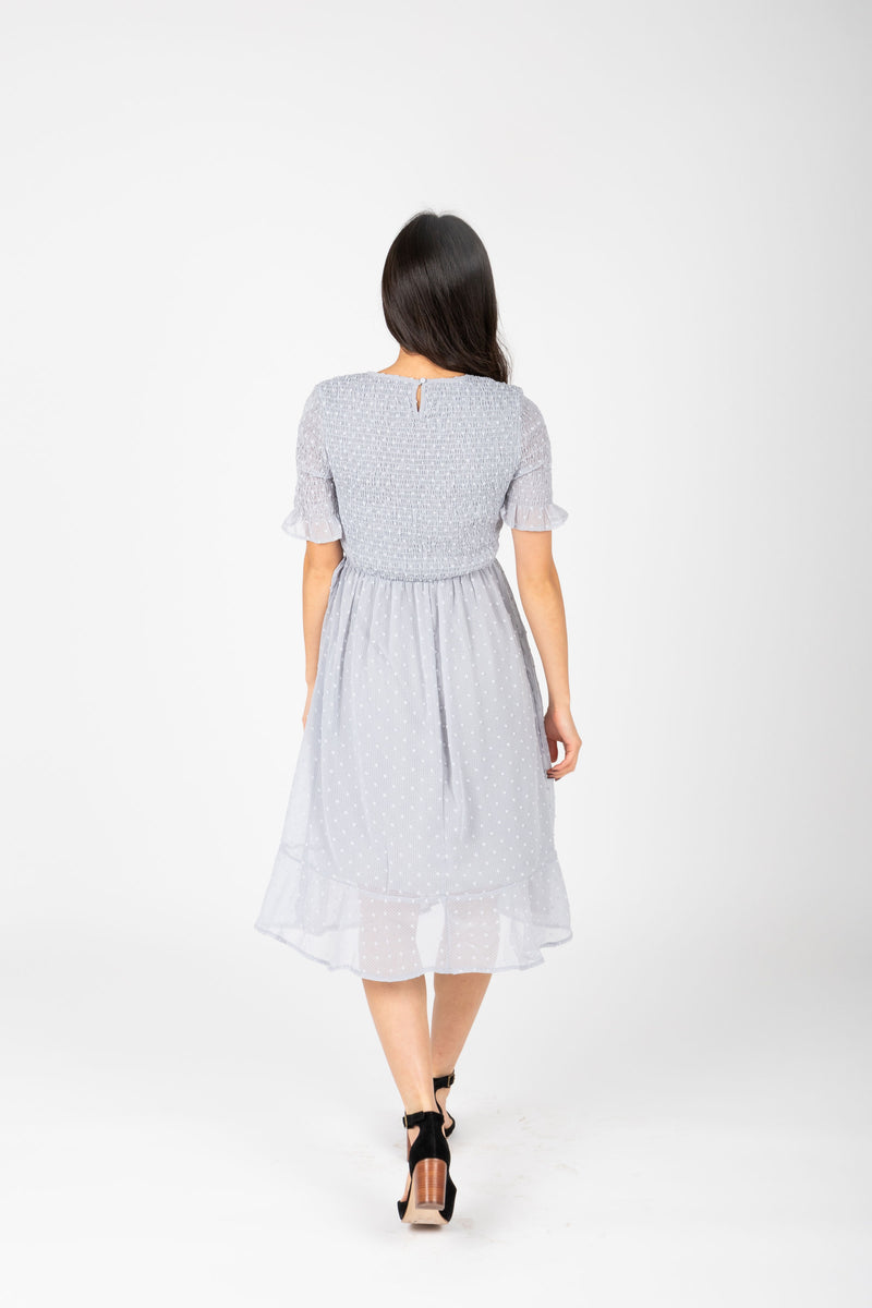 The Sandra Smocked Swiss Dot Blouse in Powder Blue, studio shoot; back view