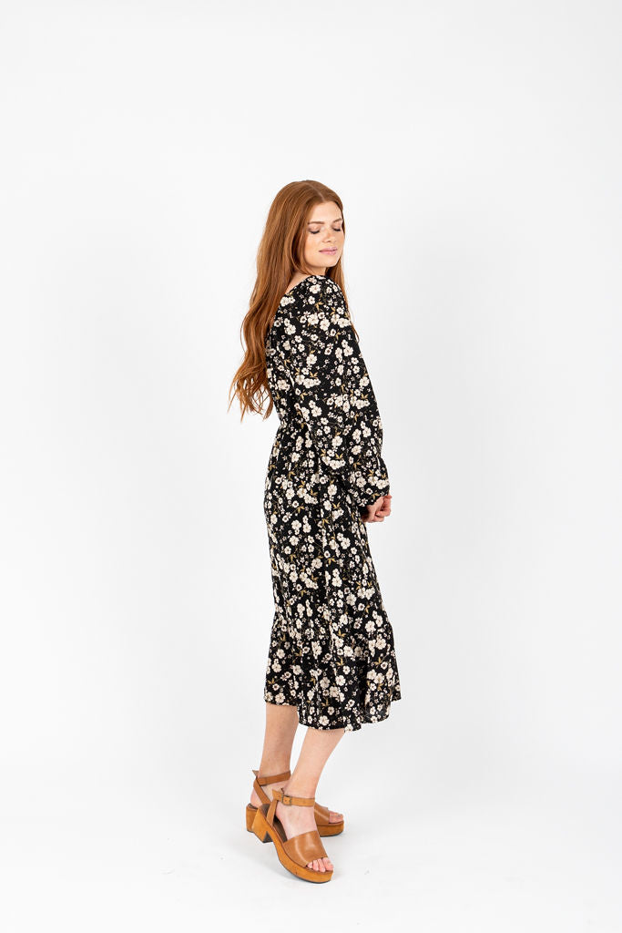 The Forsey Floral Smocked Midi Dress in Black, studio shoot; side view