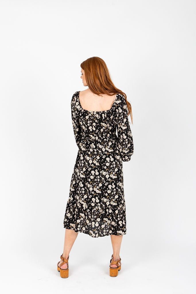 The Forsey Floral Smocked Midi Dress in Black, studio shoot; back view