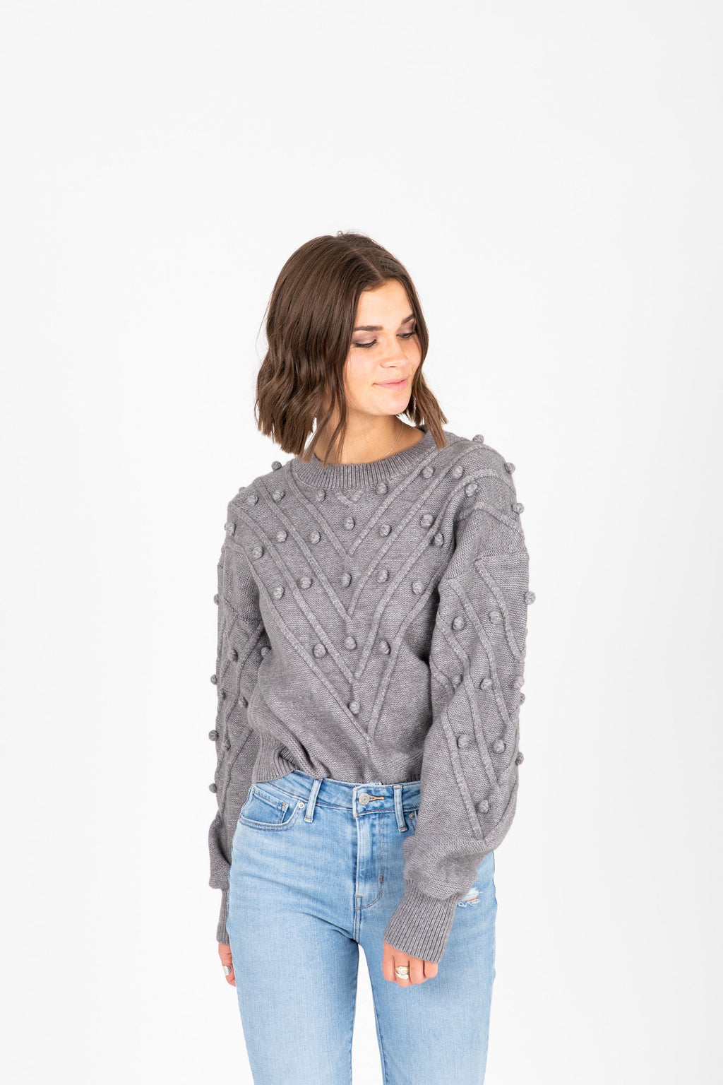 The Jennifer Pom Knit in Charcoal, studio shoot; front view