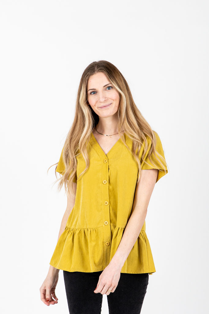 The Carr Button Peplum Blouse in Mustard, studio shoot; front view