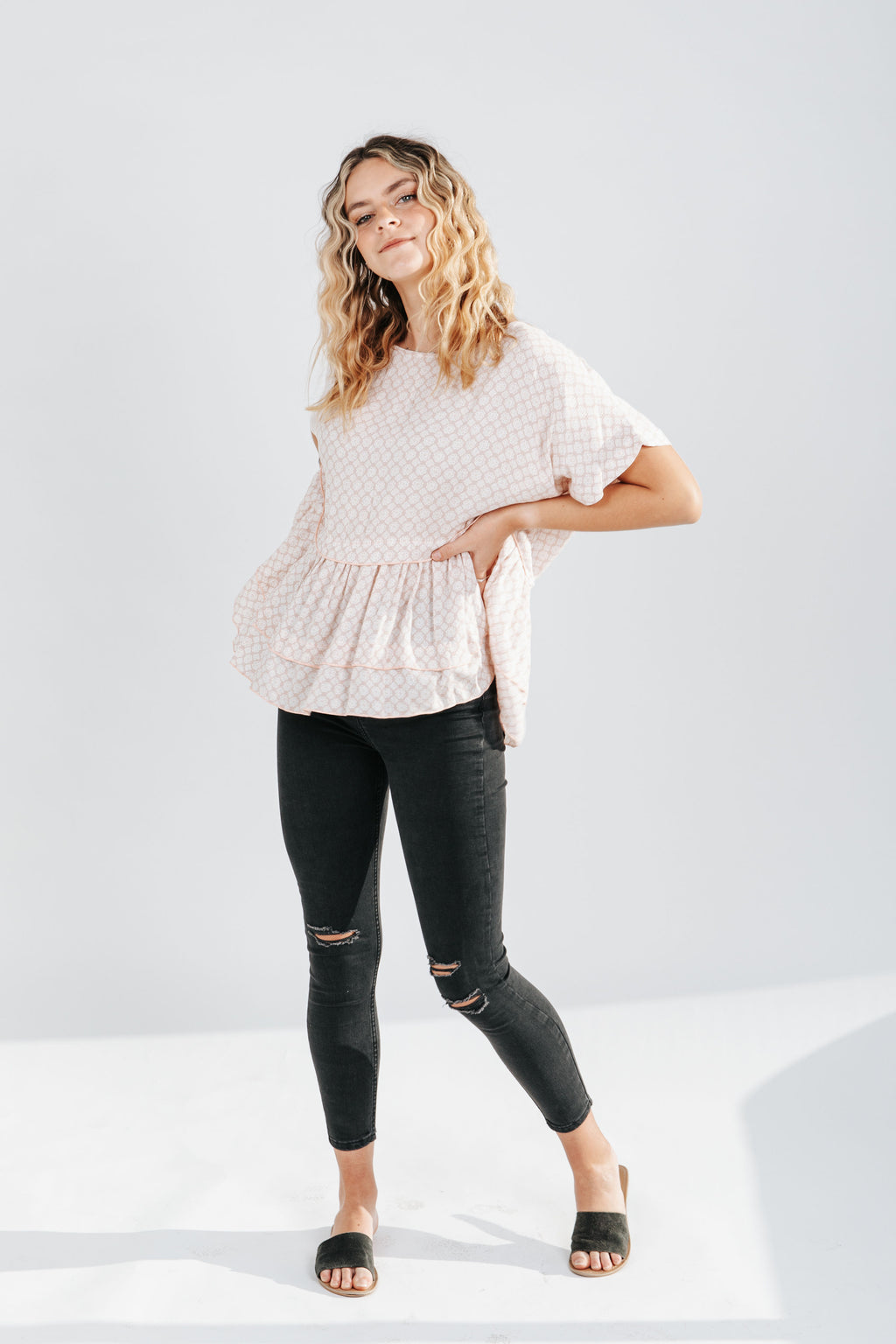 The Sally Patterned Peplum Blouse in Blush, studio shoot; front view