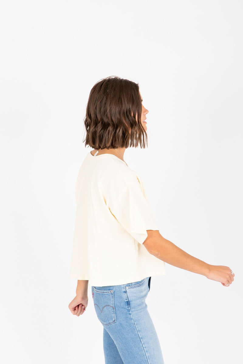 The Jay Button Tee in Cream, studio shoot; side view