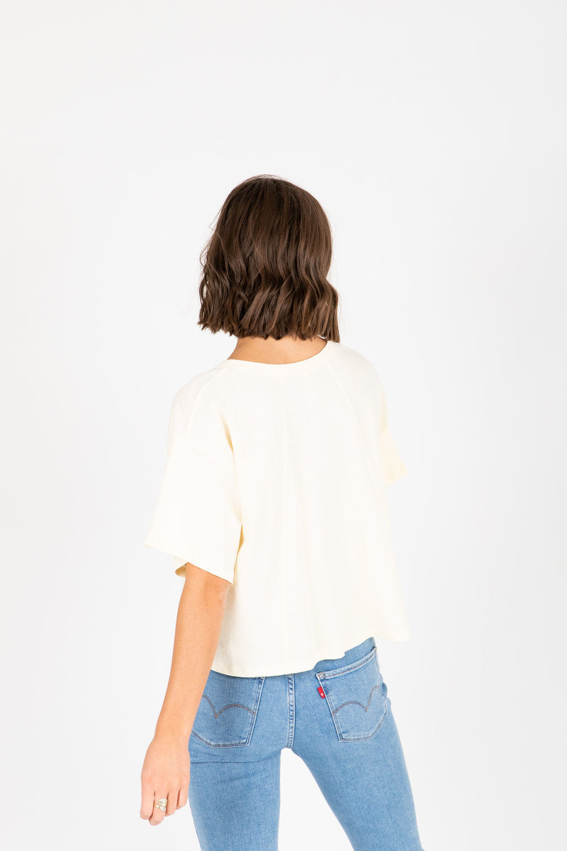 The Jay Button Tee in Cream, studio shoot; back view