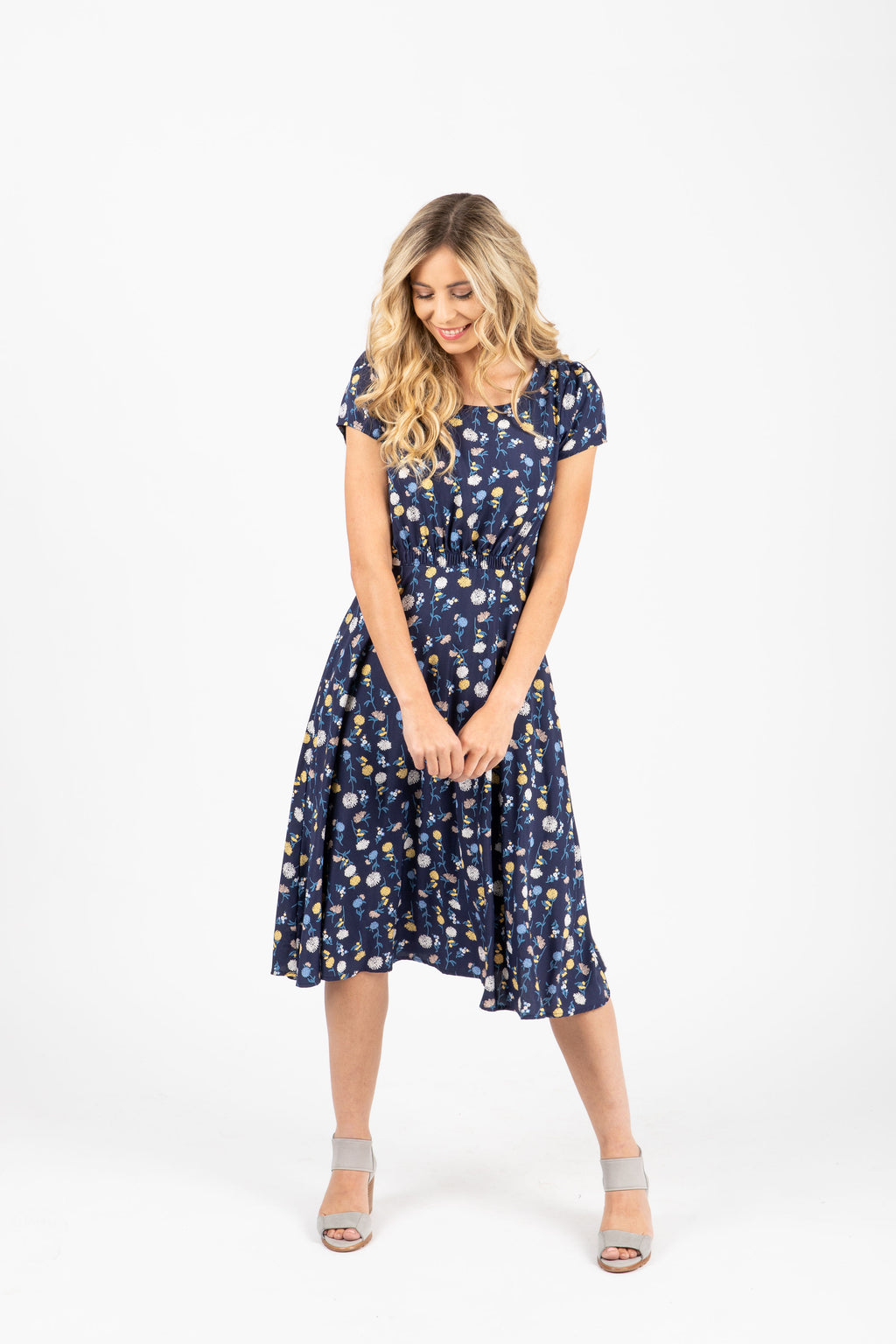 The Percey Floral Pleated Dress in Navy, studio shoot; front view