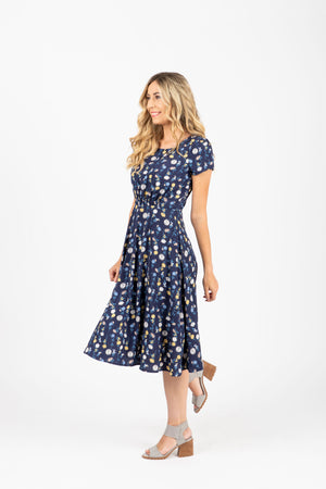 The Percey Floral Pleated Dress in Navy, studio shoot; side view
