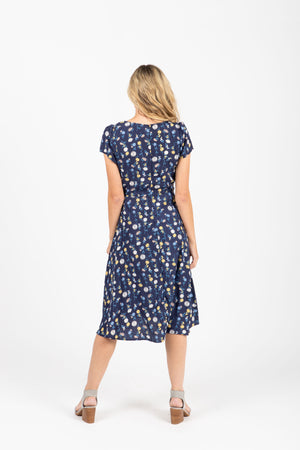 The Percey Floral Pleated Dress in Navy, studio shoot; back view