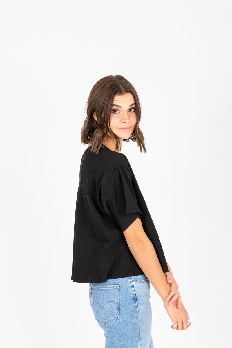 The Jay Button Tee in Black, studio shoot; side view