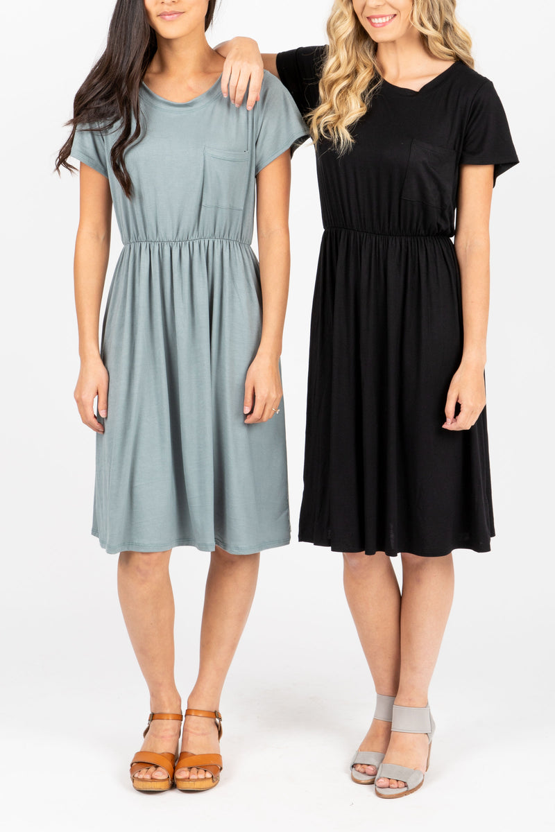 The Madeleine Casual Empire Dress in Black- studio shot; front view with sage dress as well