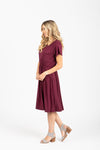 The Madeleine Casual Empire Dress in Plum- studio shoot; side view